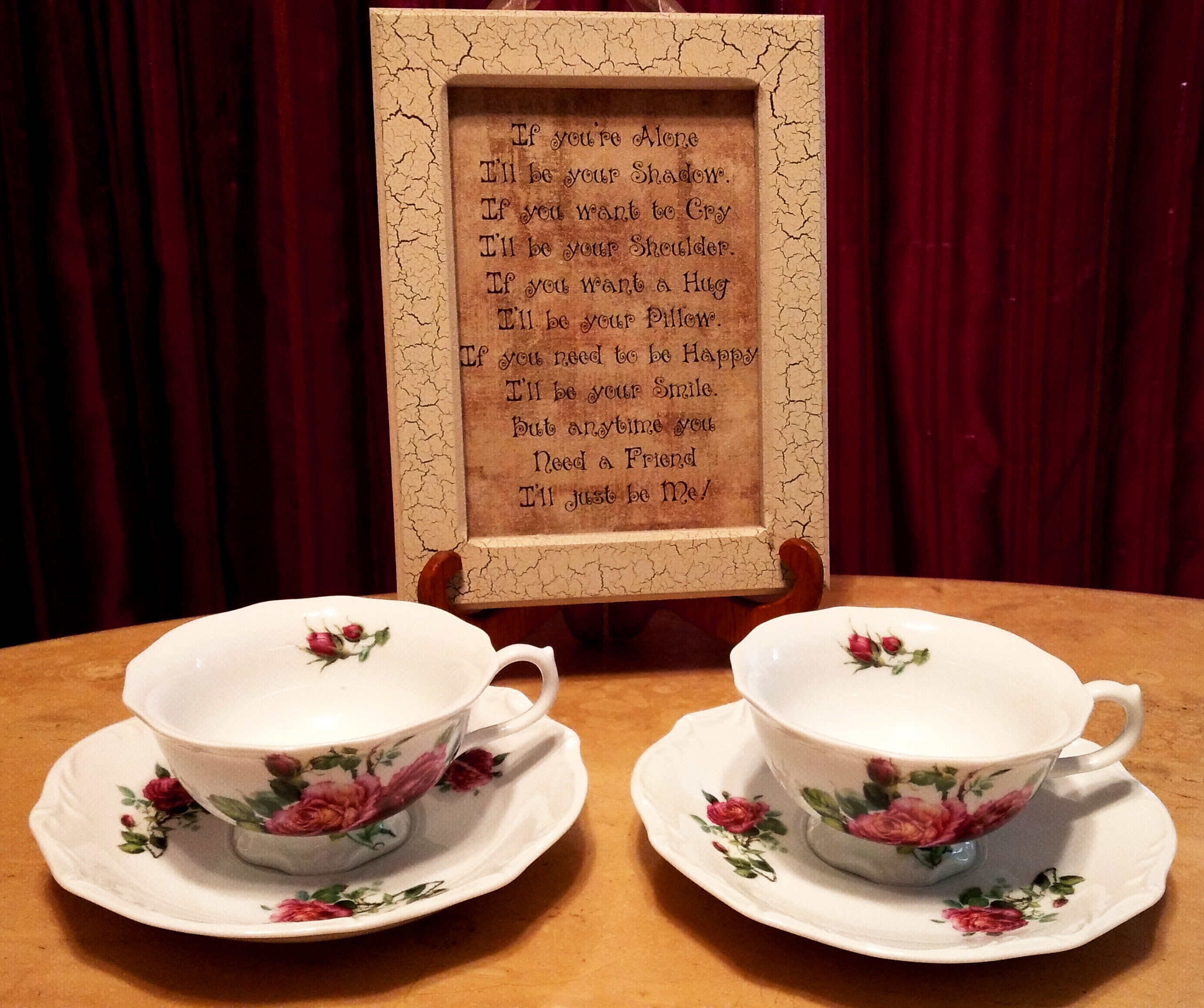 Two teacups on saucers in front of placard with dark background