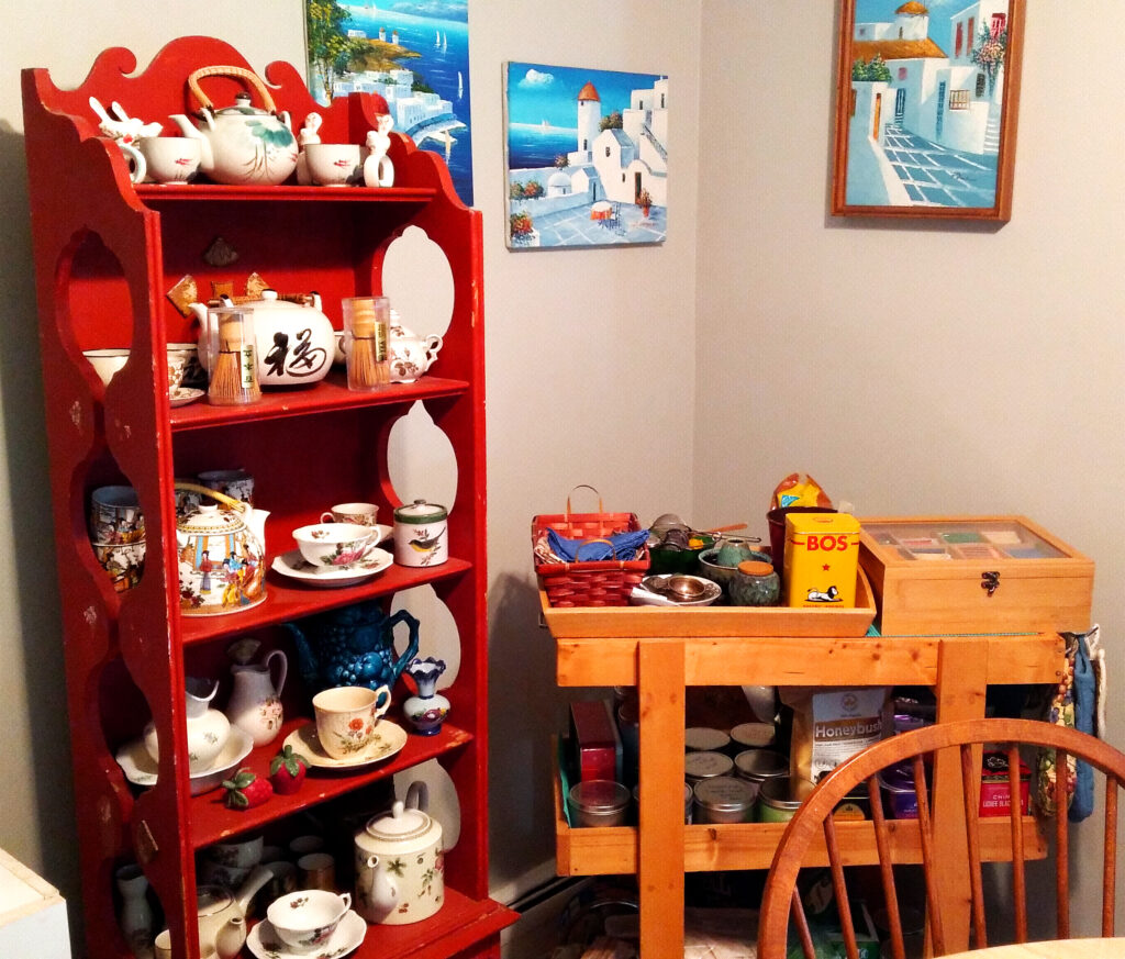 red shelf filled with china, cart filled with tea