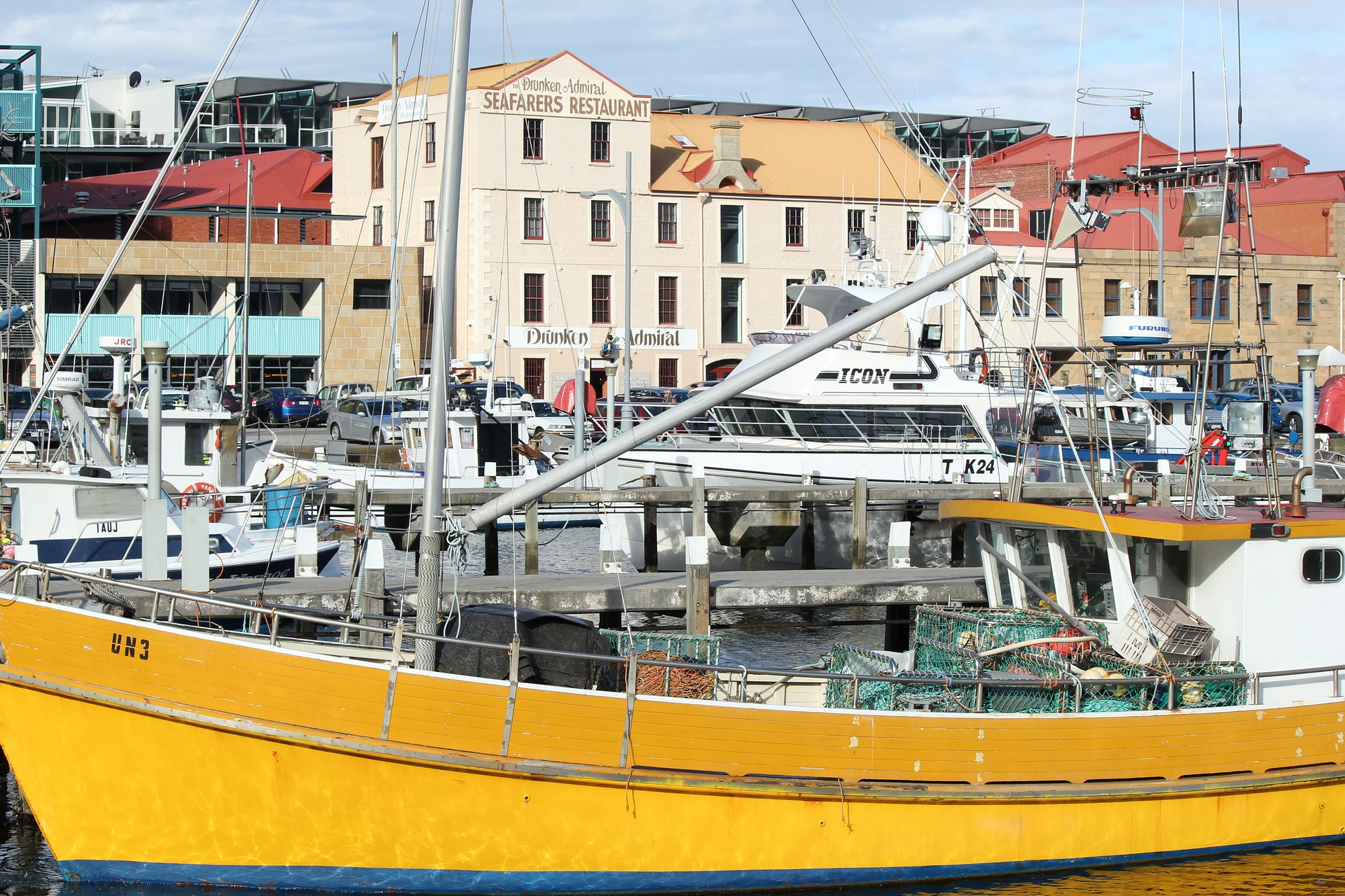yellow and white boat resting at a busy dock, city buildings in background