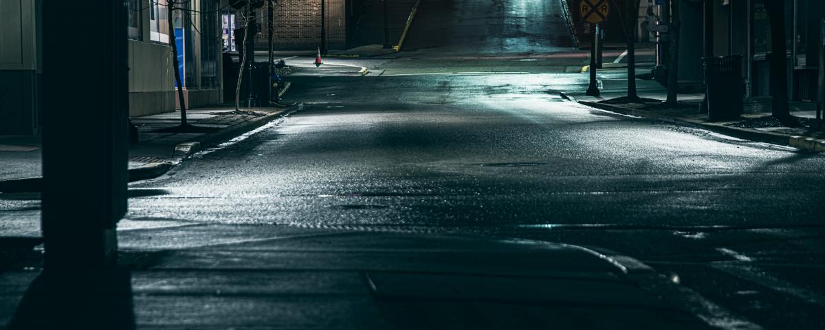 Dark street at night, a few small lights shining
