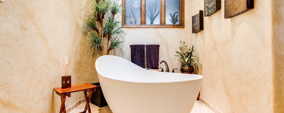 bathtub in lovely bathroom, live plants, table with candle and window visible
