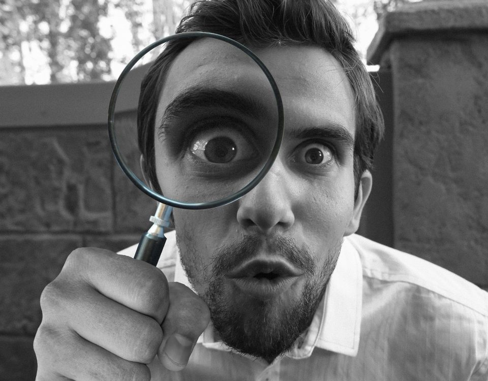 Black and white image of man with magnifying glass over one eye, looking comical
