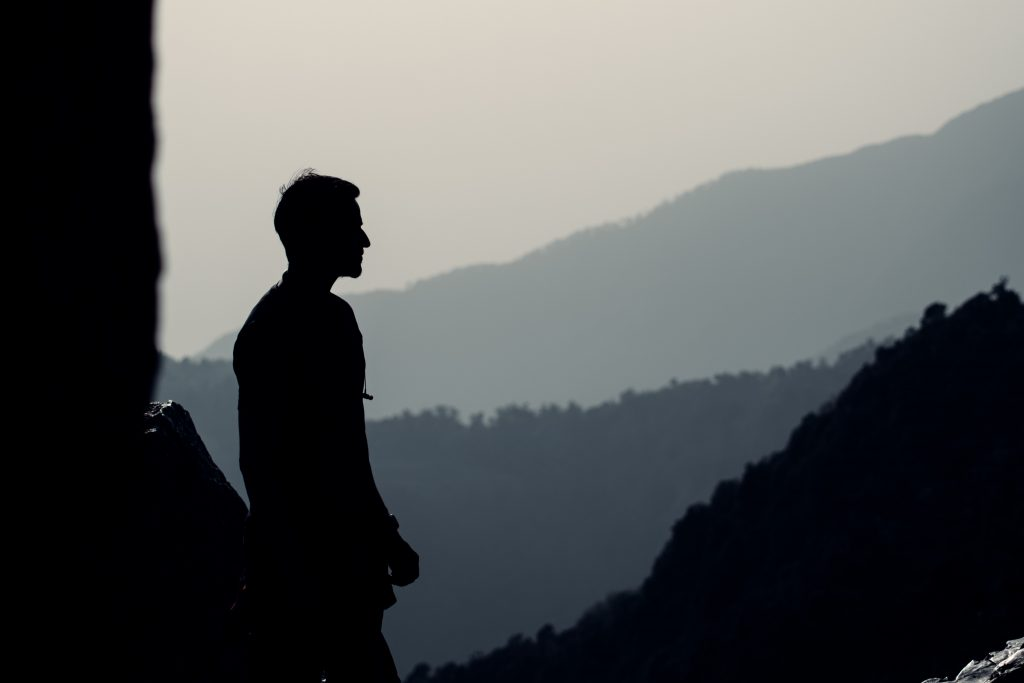 man in shadow with mountains in background